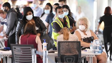 Incoming passengers are screened by police as they arrive at the domestic terminal at Brisbane Airport.