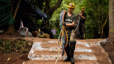 Thai volunteers bring back to the base camp the fibre optic cables that have failed to work inside the cave.