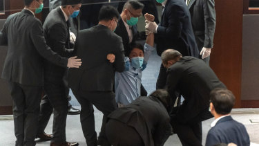 Pro-democracy member of the Hong Kong Legislative Council Ted Hui Chi-fung being removed by security during a scuffle with pro-Beijing legislators.
