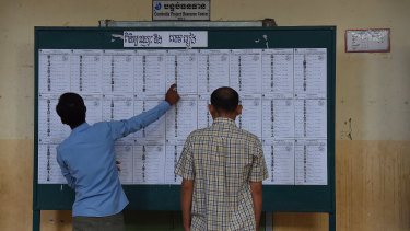 Cambodian men search for their names on the voter lists during the  election at Kandal Provincial Teacher Training School.