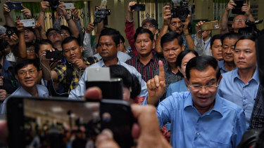 President of the Cambodian People's Party Hun Sen raises his finger indicating he has voted.