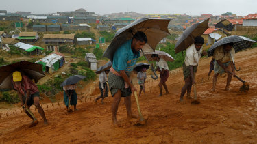 A group of men work in the rain to create drainage on the side of a cliff in preparation for overdue monsoon rains.