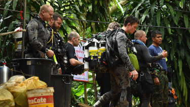 Members of the Australian Federal Police dive team walk down the track that leads to the cave entrance where the rescue operations are being planned.