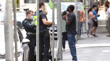 Police officers in the city stop a man and ask him to put on a mask.