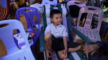 Beam Wongsookjan, 5, watching footage of his brother of Akekarat Wongsookjan 14, who is trapped in the cave.