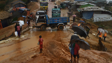 Trucks, rickshaws and people negotiate their way through the mud after a monsoon downpour in Kutupalong Camp this week.