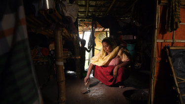 Rohingya refugee Asmida Khatun, 30, smooths out cement on the floor of her family's shelter.