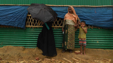 Rohingya women take shelter during a monsoonal downpour in Hakim Para Camp this week.