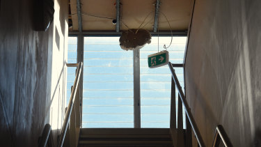 A fire exit sign was dangling from the ceiling at the site of the abandoned apartments on Tuesday.