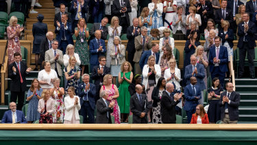 Royals and spectators stand for Sarah Gilbert, seated at bottom right, at Wimbledon's Centre Court.