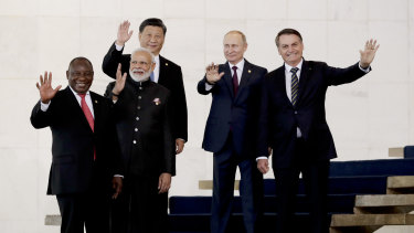 From left to right, South Africa's President Cyril Ramaphosa, India's Prime Minister Narendra Modi, China's President Xi Jinping, Russia's President Vladimir Putin and Brazil's President Jair Bolsonaro wave to photographers during the BRICS Summit in Brasilia.