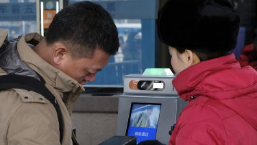 A passenger at Beijing Railway Station goes through a self-service ticket checking machine by getting his face recognised and ID card scanned. This is then linked to data to see if the person is on a black list.