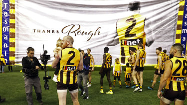 Memorable exit: Jarryd Roughead of the Hawks carries his daughter Pippa through the banner before the game against Gold Coast.