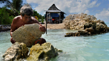 A homeowner in the Kiribati Islands rebuilds a sea wall to protect his house on the island of Tarawa.
