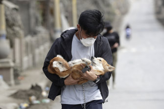 An animal rescue volunteer carries a dog found among deserted homes near the Taal volcano.