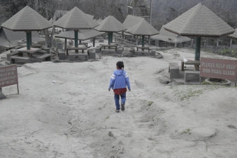 A woman walks through a park blanketed in ash in the town of Tagaytay, near the Taal volcano.