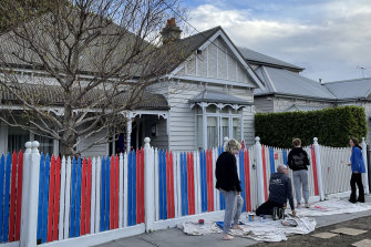 A family paints the front fence of their Seddon home in the red, white and blue of the Western Bulldogs.