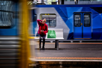 A woman waits at an almost-empty Southern Cross station.