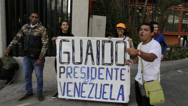 """Anti-government protesters show a sign that reads in Spanish """"Guaido President of Venezuela"""" after a rally demanding the resignation of President Nicolas Maduro in Caracas, Venezuela."""
