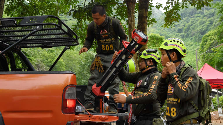 Thai volunteers arrive at the base camp where the rescue operations are being planned for the 12 boys and their soccer coach.