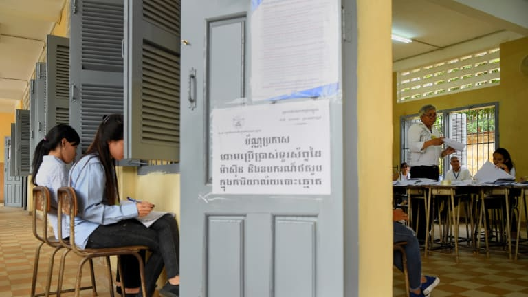 An election official counts the votes from the Cambodian election as two women independently record the count.