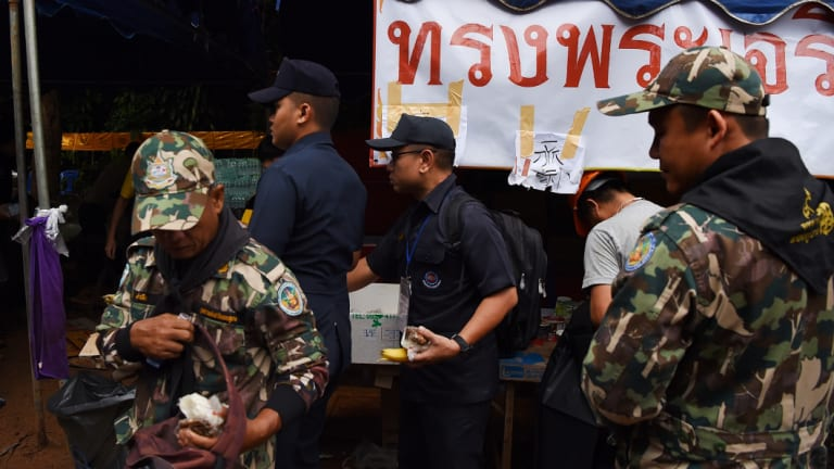 Thai rescuers collect food at the base camp at Tham Luang Cave.