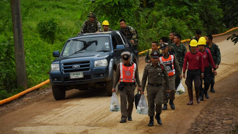 Thai police and military walk towards the cave on Wednesday morning.