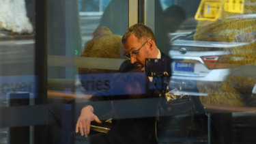 One of three AFP officers sits in the reception of the ABC offices in Ultimo