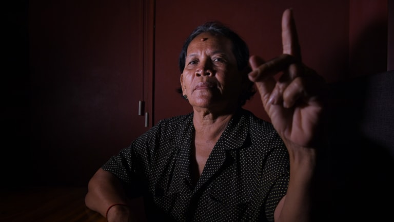 Bou Sokhom holds up a clean finger to indicate she will be boycotting Cambodia's general election.