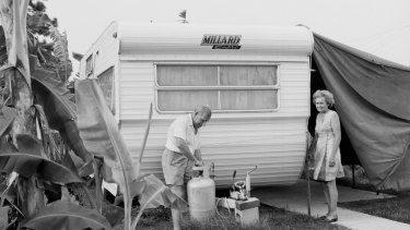 A retired couple change the gas bottle on an Australian-made Millard Capri caravan.