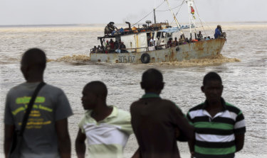 A boat brings displaced families ashore after they were rescued from a flooded area of Buzi district, 200 kilometres from Beira in Mozambique on Saturday.