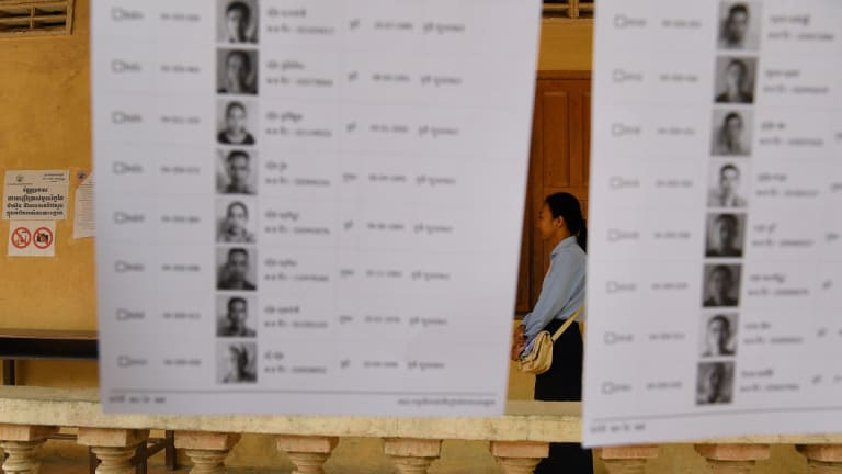 An election official stands among the voter lists at a polling station.