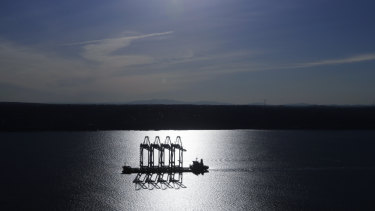 A heavy-lift ship carrying four  container cranes is silhouetted by the sun near Tacoma, Washington. Most economists were already worried that the odds of a recession are rising, and most of the worries stem from the U.S.-China trade war.