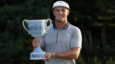 On fire: Bryson DeChambeau holds the trophy aloft for the second consecutive week.