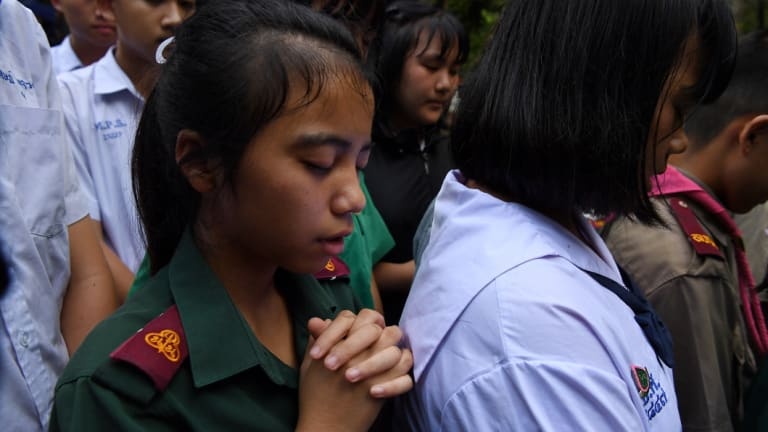 Friends and classmates of the trapped boys in Tham Luang cave gather at the staging area to pray for their safe return.