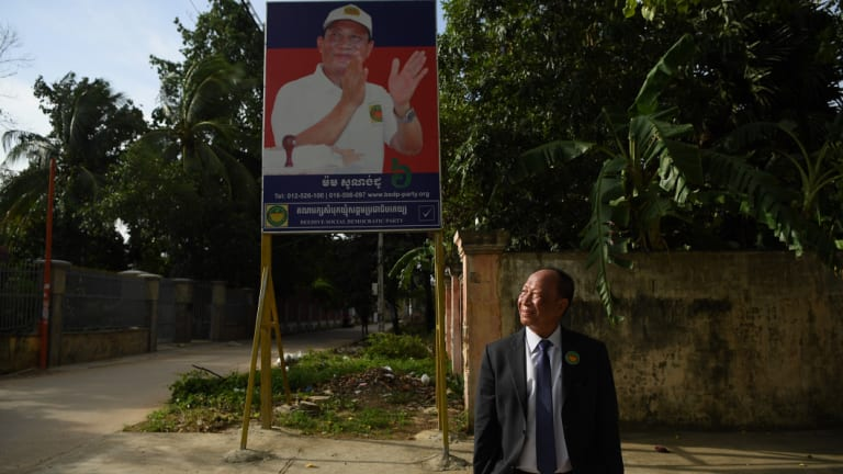 Mam Sonando stands in front of his campaign banner at the Beehive Social Democratic Party headquarters outside Phnom Penh.