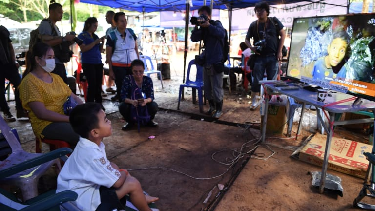 Beam Wongsookjan, 5, second from left,  watches footage of his older brother and the other boys.