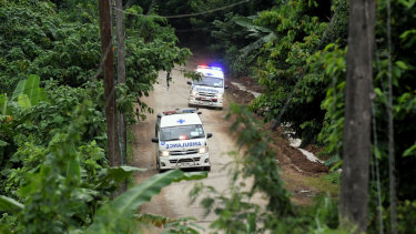 Ambulances carrying the 10th and 11th boys rescued drive away from the cave.