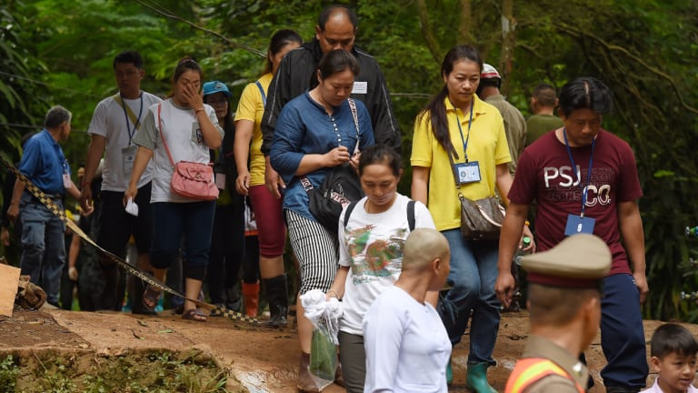 The families of the trapped boys and their coach return from praying at Tham Luang cave on Saturday.