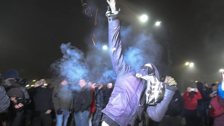 A protester throws a smoke grenade during a rally in front of the embassy of Russia in Kiev, Ukraine, on Sunday.