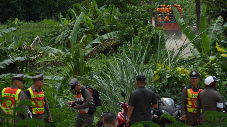 Thai rescue volunteers make their way up to the base camp near Tham Luang cave on Monday.