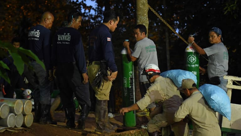 Rescuers move extra supplies of oxygen near the cave on Thursday.