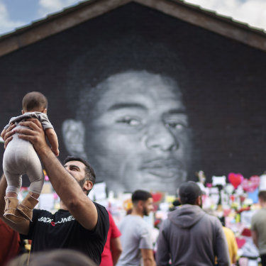 A man holds a child in the air as crowds gather at the Marcus Rashford mural in Manchester.