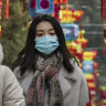 Women and a child wear protective masks in Beijing, China, on Saturday.