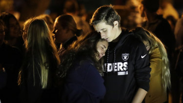 Hannah Schooping-Gutierrez, centre, a student at Saugus High School, is comforted by her boyfriend Declan Sheridan, at right.