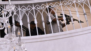 Supporters of Kyrgyzstan's ex-president Almazbek Atambayev hold their weapons during the raid at his home.