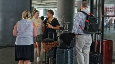 Tourists, freshly presented with frangipani necklaces by one of the women employed solely to do so, arrive at Bali international airport.