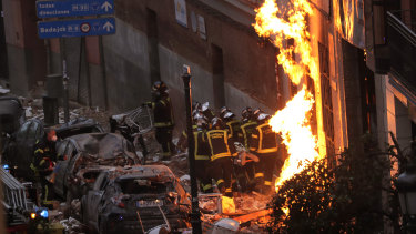 Fire-fighters carry a victim next to a damaged building at Toledo Street following a powerful explosion in downtown Madrid, Spain.