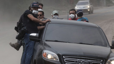 Rescuers and journalists evacuate the disaster zone as a column of smoke and ash rises from the Volcan de Fuego, on Tuesday.