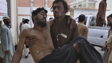 A Pakistani mine worker carries an injured colleague upon arrival at a hospital in Quetta, Pakistan.